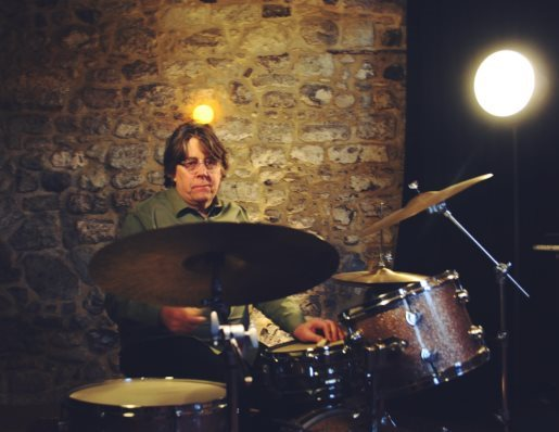 A person playing a drum setDescription automatically generated with low confidence